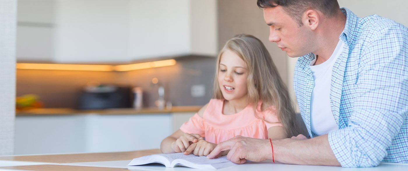 father helping daughter with dyslexia read